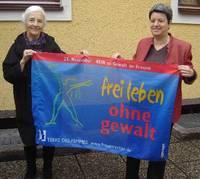 """Gertrude Piontek und Nicole Adam halten die Flagge """"frei leben""""."""