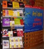 """Infoständer mit Broschüren gegen Gewalt und Flagge """"frei leben"""" im Foyer der Gemeide."""