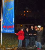"""Mehrere Personen beim Hissen der Flagge """"frei leben"""" am Rathauspark."""
