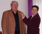 "Obfrau Gertrude Piontek steckt Bürgermeister Herwart Loidl eine ""weiße Schleife"" an."