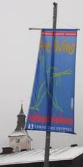 """Fahne """"frei leben"""" mit Kirchenturm von Ebensee im Hintergrund."""