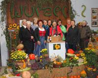 Teilnehmerinnen der Weiberroas am Wurzer Hof mit Obst und Gemüse im Vordergrund.