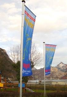"""2 Flaggen """"frei leben"""" am Rathauspark mit Gebirge im Hintergrund."""