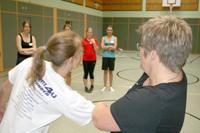 Selbstverteidigungstrainerin mit Schülerin beim Vorführen einer Übung